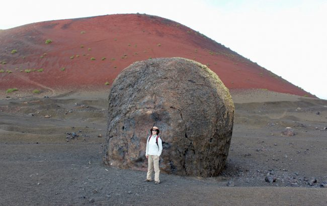 Standing in front of the volcanic bomb, with Montaña Colorada in the background (walking on Lanzarote)