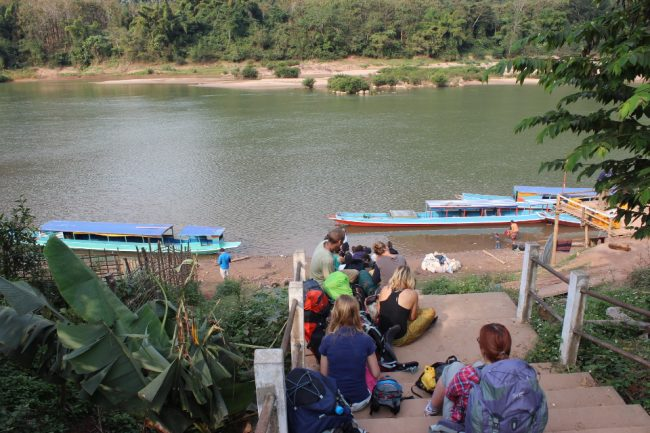 Travellers with their gear waiting for the boat in Muang Noi, Laos (best safety tips)